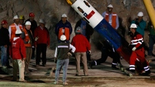 Rescue workers and officials test the capsule that will be used to extract 33 trapped miners one by one from the collapsed San Jose Mine near Copiapo, Chile, Tuesday Oct. 12, 2010. (AP / Roberto Candia)